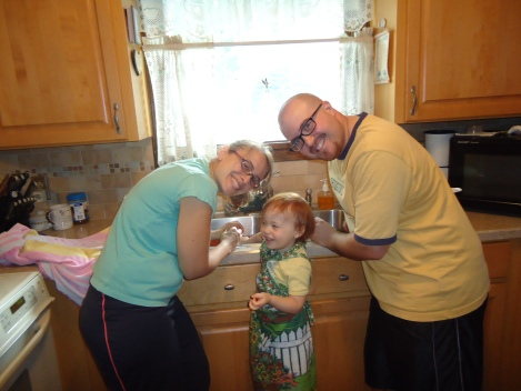 To prep the berries, they need to be washed and hulled (have the leafy parts taken off the top). Here is me and my sis-in-law and my oldest daughter. The OD actually volunteered to help and then didn't want to take any breaks. She has her mother's work ethic.